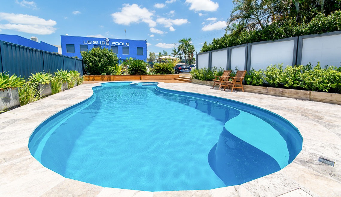 Leisure Pools Allure freeform inground swimming pool with built-in spa and splash deck