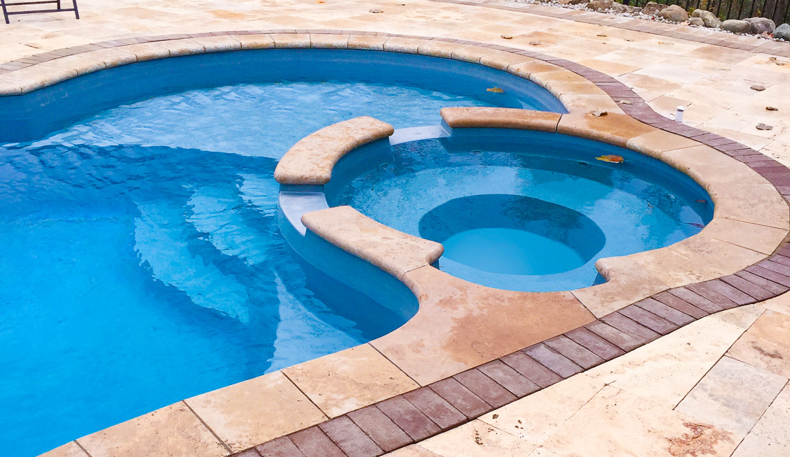 Leisure Pools Allure large freeform swimming pool with built-in spa and splash deck